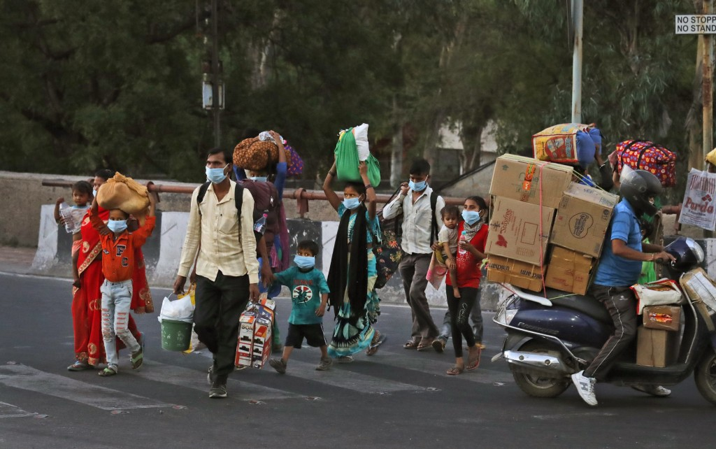 A migrant worker family crosses a street as they leave city to go back to their villages during a nationwide lockdown to curb the spread of new corona...