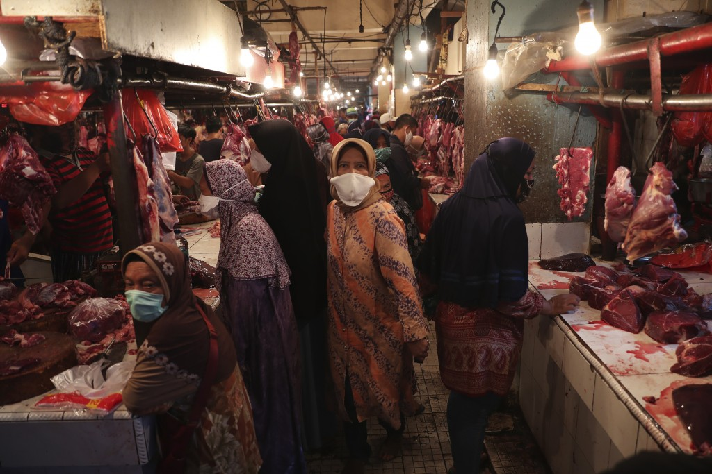 Muslim women shop for meat in preparation of the upcoming Eid al-Fitr holiday that marks the end of the holy fasting month of Ramadan amid fears of th...
