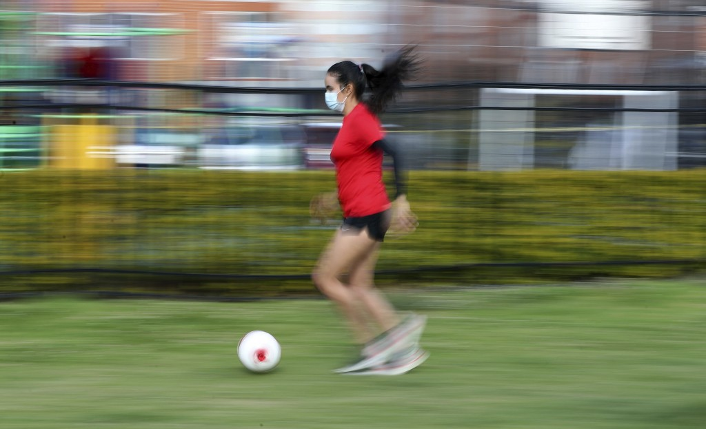 Wearing a face mask, Venezuelan soccer player María Alejandra Peraza, who played last season with Colombia's Millonarios women's team, trains alone at...