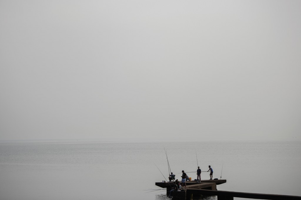 People fish from a wharf in Montevideo, Uruguay, Wednesday, May 20, 2020. (AP Photo/Matilde Campodonico)