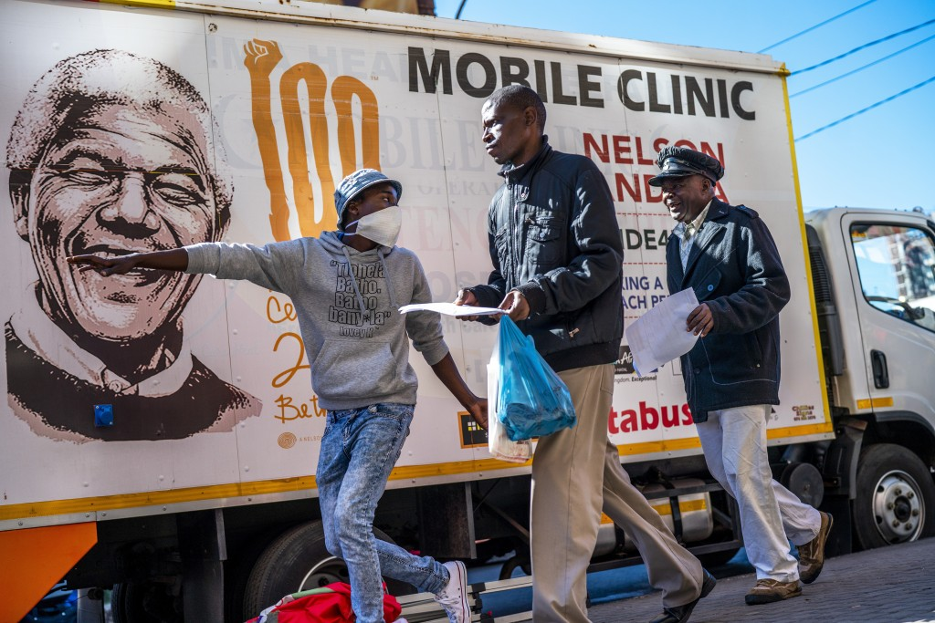 A volunteer directs two men towards a medical tent where they will be tested for COVID-19 as well as HIV and Tuberculosis, in downtown Johannesburg, A...