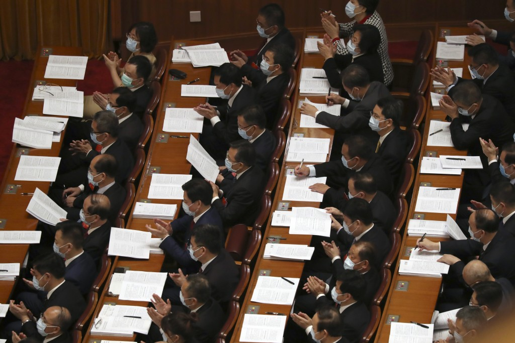 Delegates applaud during the opening session of China's National People's Congress (NPC) at the Great Hall of the People in Beijing, Friday, May 22, 2...