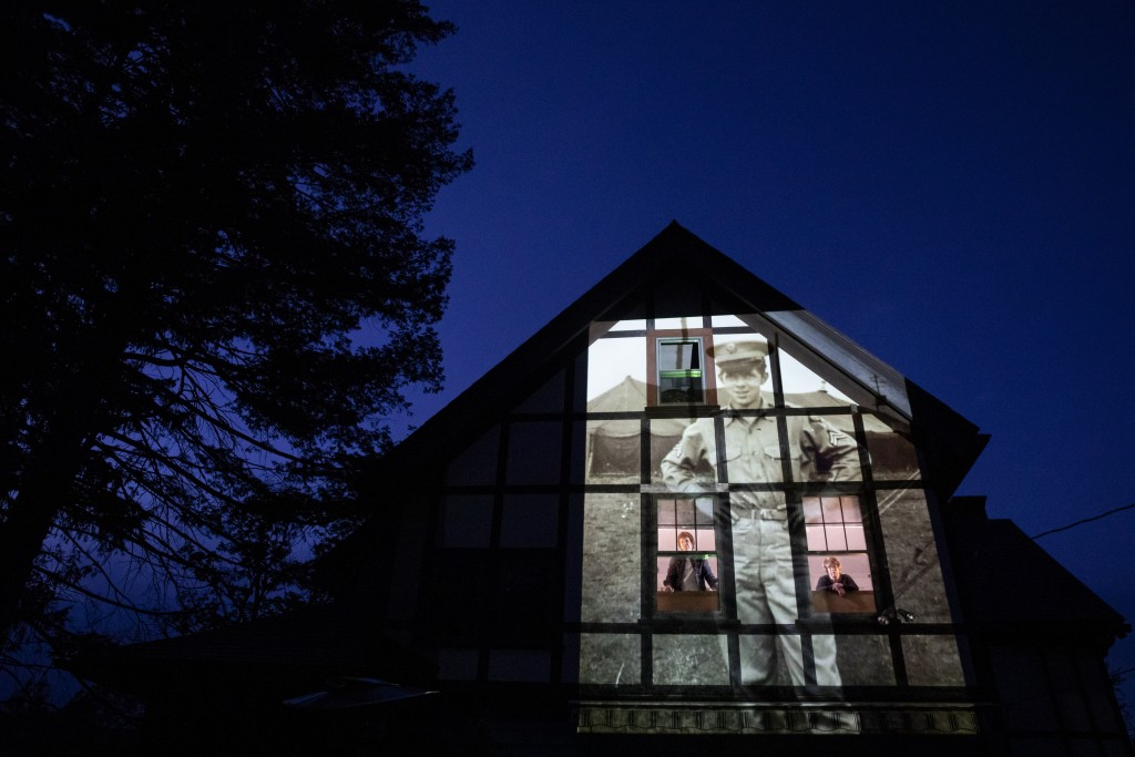 An image of veteran Alfred Healy is projected onto the home of his daughter, Eileen Driscoll, left, as she looks out the window with her sister, Patri...