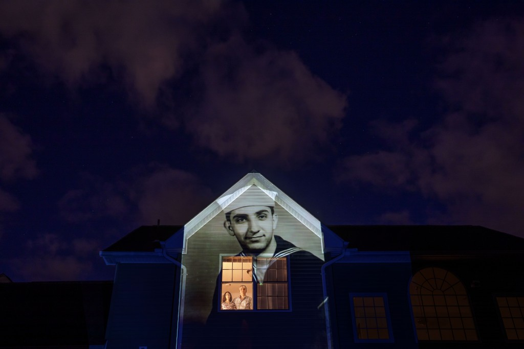 An image of veteran Harry Malandrinos is projected onto the home of his son, Paul Malandrinos, as he looks out a window with his wife, Cheryl, in Wilb...