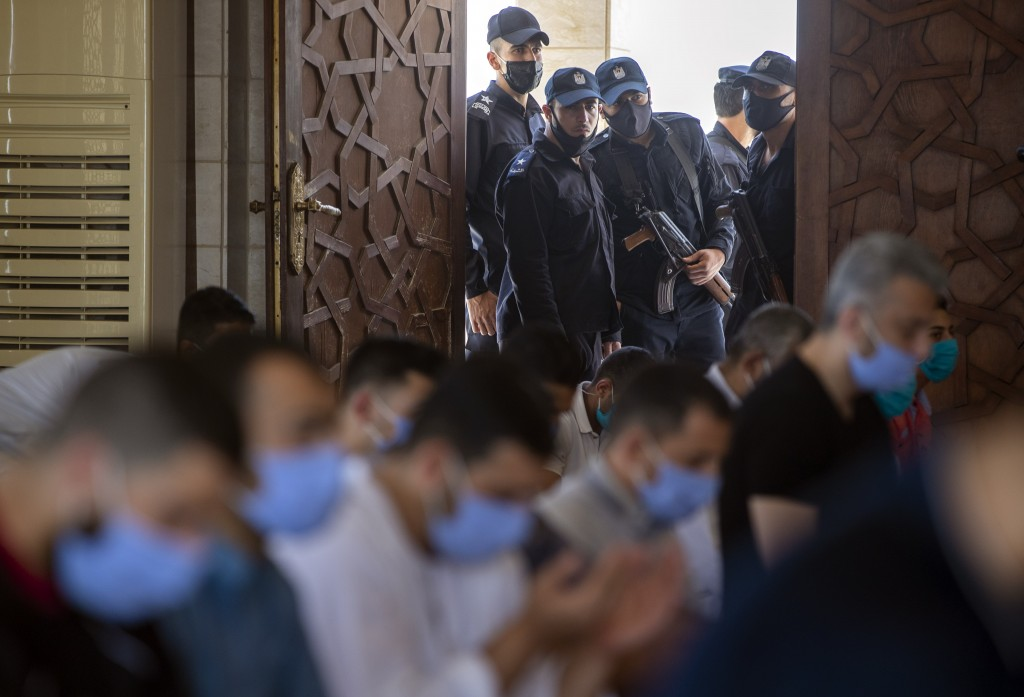 Palestinian Hamas police stand guard at the entrance of a mosque as worshipers attend the last Friday noon Prayer of the holy month of Ramadan, in Gaz...