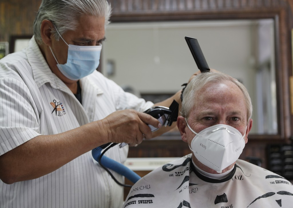 Barber Rudy Soliz gives Brian Barnett a haircut at the San Marcos Barber Shop in San Marcos, Texas, Thursday, May 21, 2020. Businesses in Texas closed...