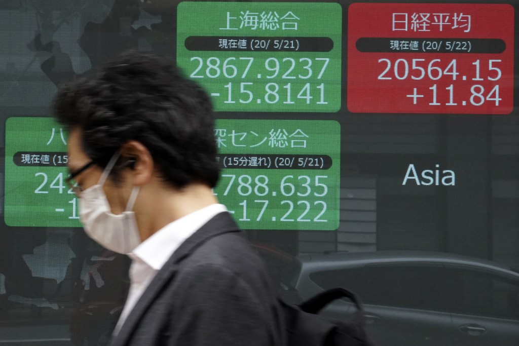 A man walks past an electronic stock board showing Japan's Nikkei 225 and other Asian indexes at a securities firm in Tokyo Friday, May 22, 2020.  Sha...