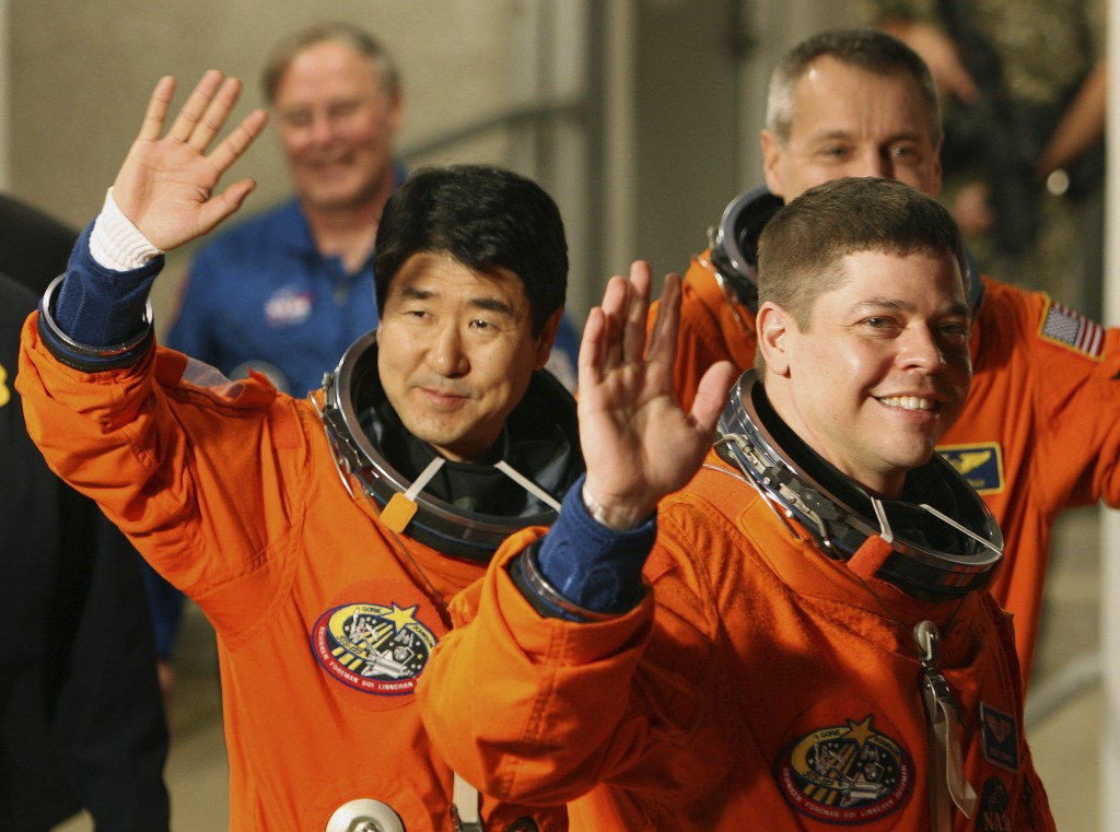 FILE - In this Monday evening, March 10, 2008 file photo, STS-123 mission specialists Takao Doi of Japan, left, Robert Behnken, foreground right, and ...