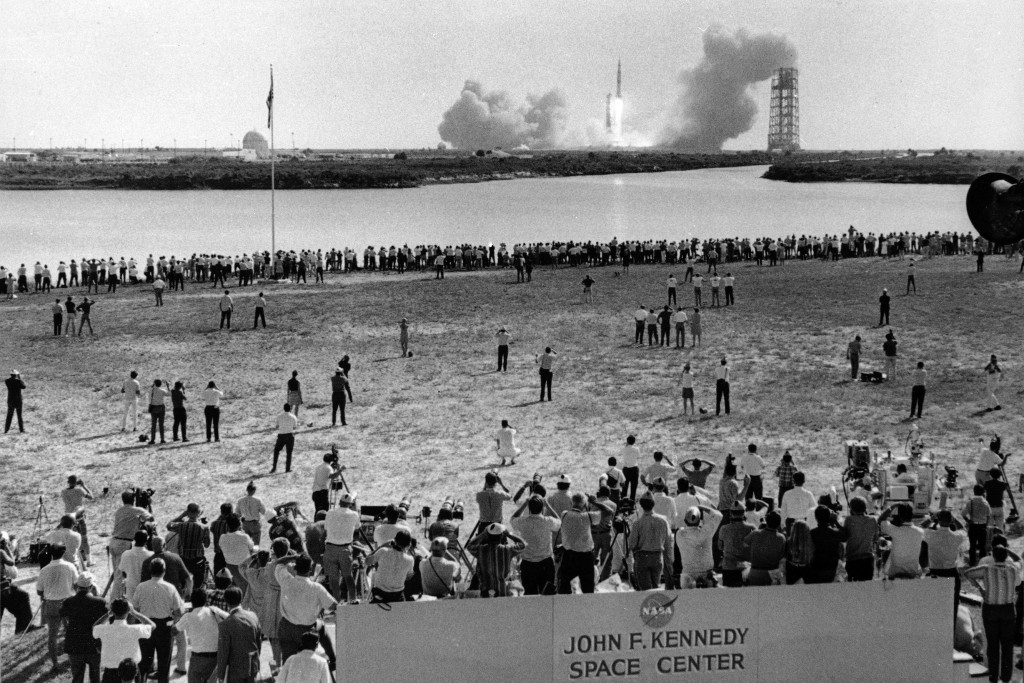 FILE - In this July 16, 1969 file photo, reporters line the banks of a lagoon at the Cape Kennedy Press Site in Cape Canaveral as the Saturn V rocket ...