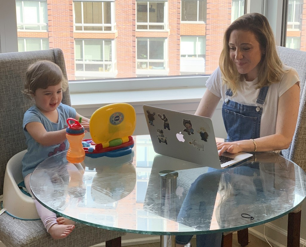 In this May 15, 2020 image, Blake Ross, founder of Kindness of Strangers, right, works on her laptop as her daughter, Tess, 2, works on her toy laptop...