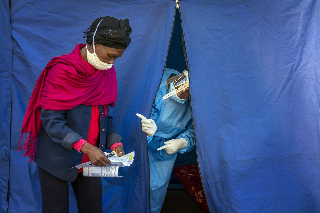 Heath officials check the listings of people who are to be tested for COVID-19 as well as HIV and Tuberculosis, in downtown Johannesburg, April 30, 20...