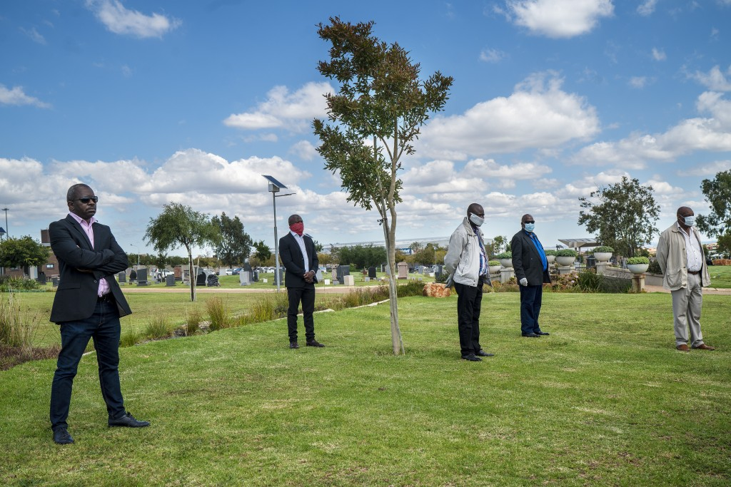 Family and friends observe social distancing during the funeral ceremony for Benedict Somi Vilakasi at the Nasrec Memorial Park outside Johannesburg, ...