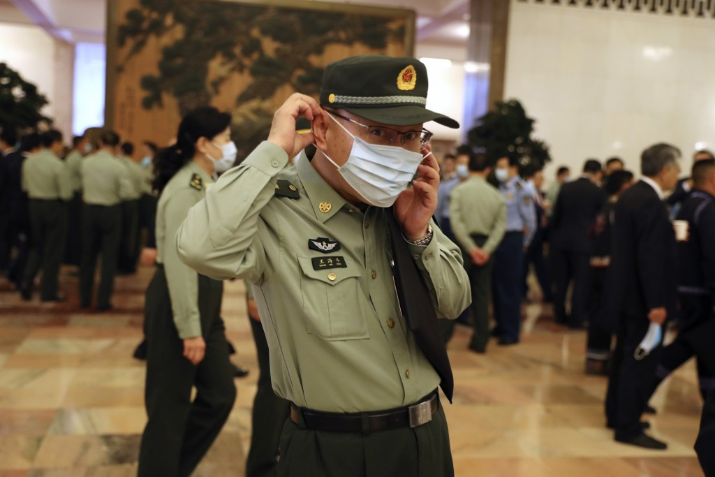 A military delegate talks on his smartphone before the opening session of China's National People's Congress (NPC) at the Great Hall of the People in ...