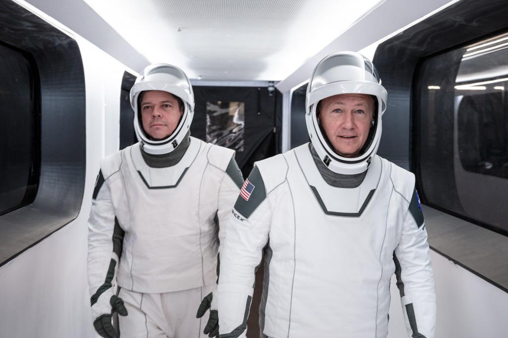 In this Jan. 17, 2020 photo made available by SpaceX, NASA astronauts Bob Behnken, left, and Doug Hurley, wearing SpaceX spacesuits, walk through the ...