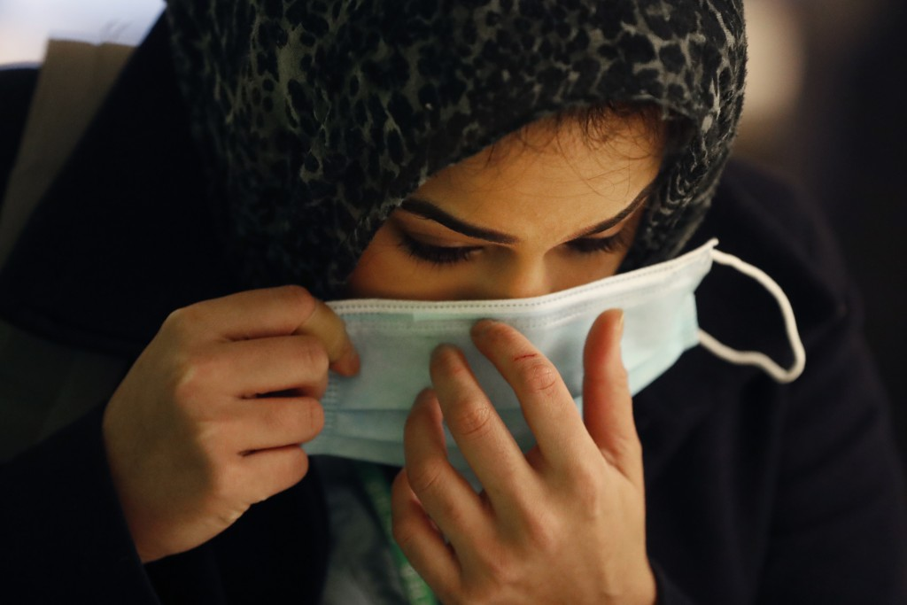 FILE - In this April 22, 2020, file photo, RUSH Hospital respiratory therapist Jumana Azam puts on a surgical mask after standing before a face temper...