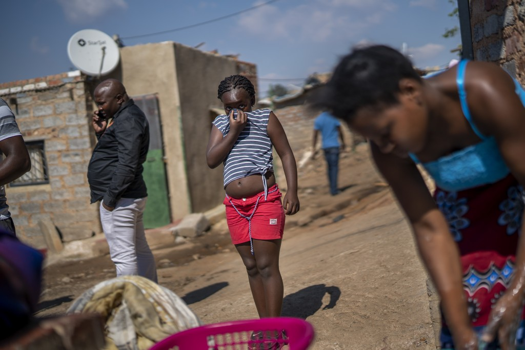 A young girl covers her face, in the Sjwetla informal settlement on the outskirt of the Alexandra township in Johannesburg, May 5, 2020, during the co...