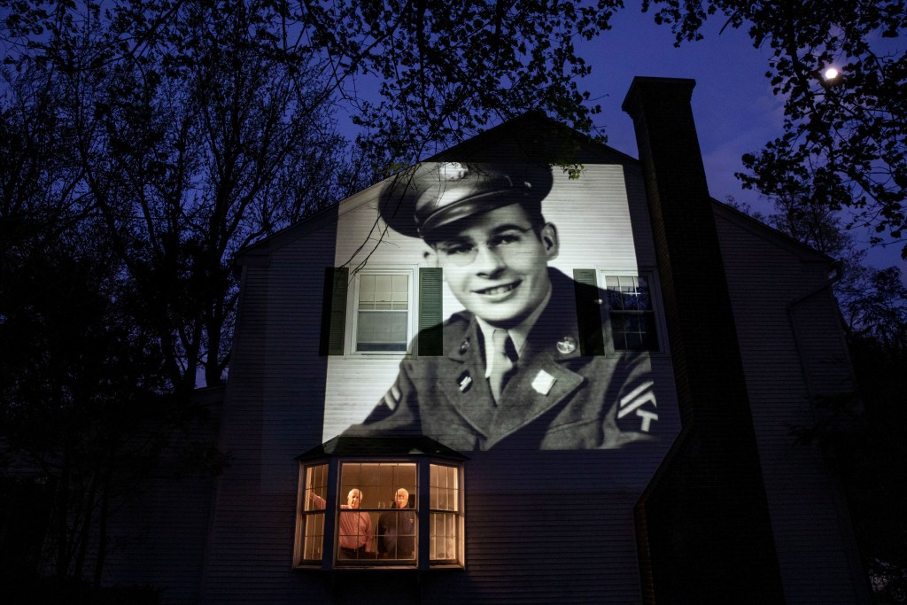 An image of veteran James Sullivan is projected onto the home of his son, Tom Sullivan, left, as he looks out a window with his brother, Joseph Sulliv...