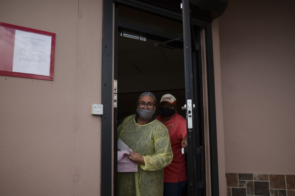 Sandra Algarin and Efrain Ortiz, employees at a health clinic, peek out the door while wearing masks as a precaution against COVID-19, in Canovanas, P...