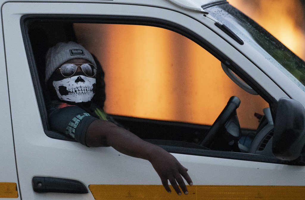 A minibus taxi driver wearing a face musk looks out the window during his journey in Kwa-Thema east of Johannesburg, South Africa, March 17, 2020. (AP...