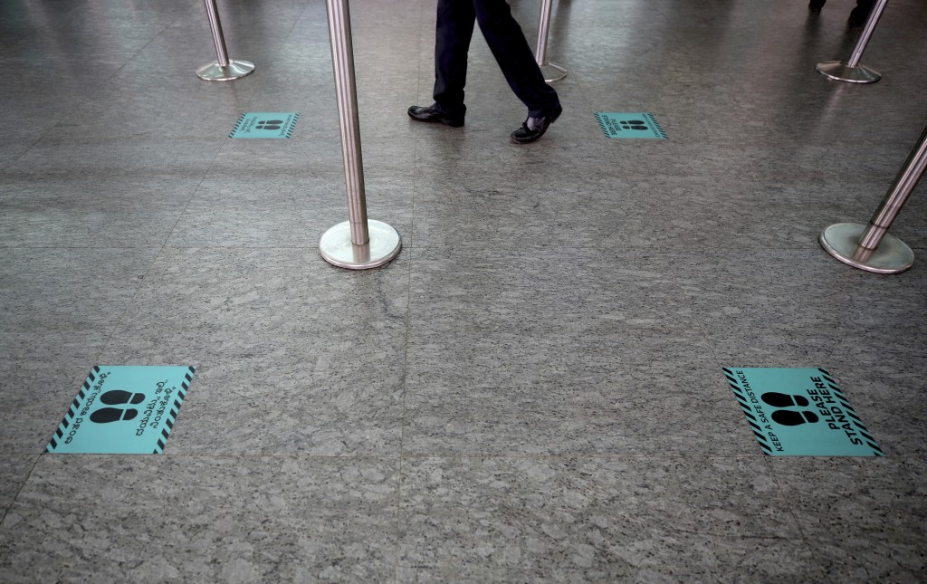 A security officer walks past newly placed markings to maintain social distancing at Kempegowda International Airport in Bengaluru, India, Friday, May...