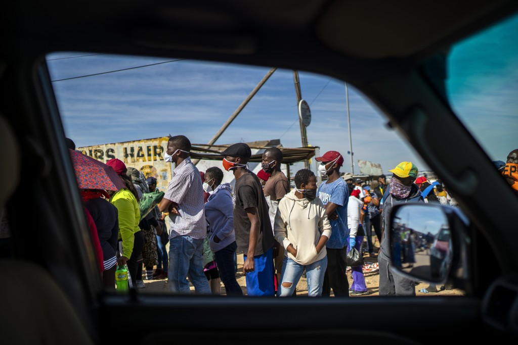 People line up to receive food handouts in the Olievenhoutbos township of Midrand, South Africa, May 2, 2020. (AP Photo/Jerome Delay)