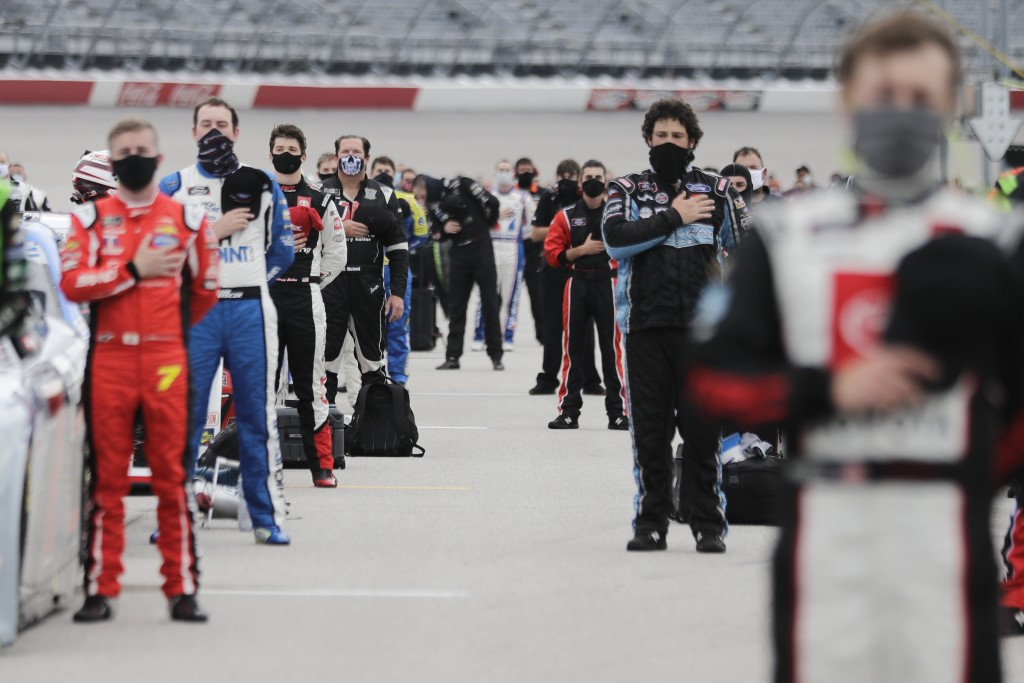 Drivers stand for the national anthem before the Toyota 200 NASCAR Xfinity series auto race Thursday, May 21, 2020, in Darlington, S.C. (AP Photo/Bryn...
