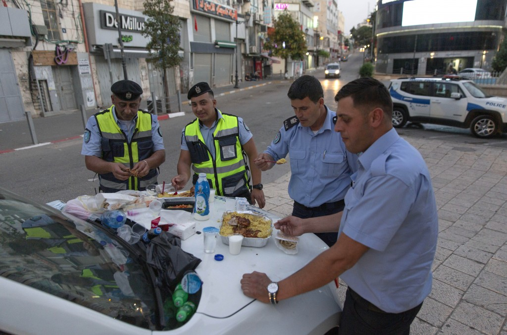 In this Tuesday, May 19, 2020, photo, Palestinian policemen have their Iftar breaking a Ramadan fasting day at the street while the state of emergency...
