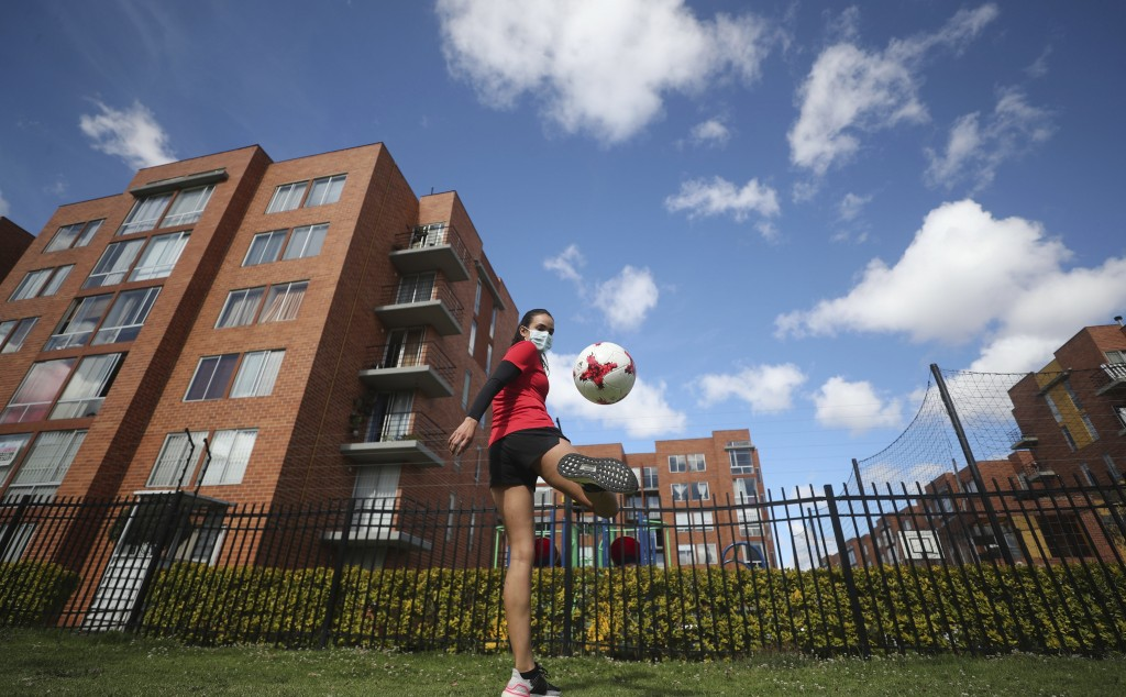 Wearing a face mask, Venezuelan soccer player María Alejandra Peraza, who played last season with Colombia's Millonarios women's team, trains in Bogot...