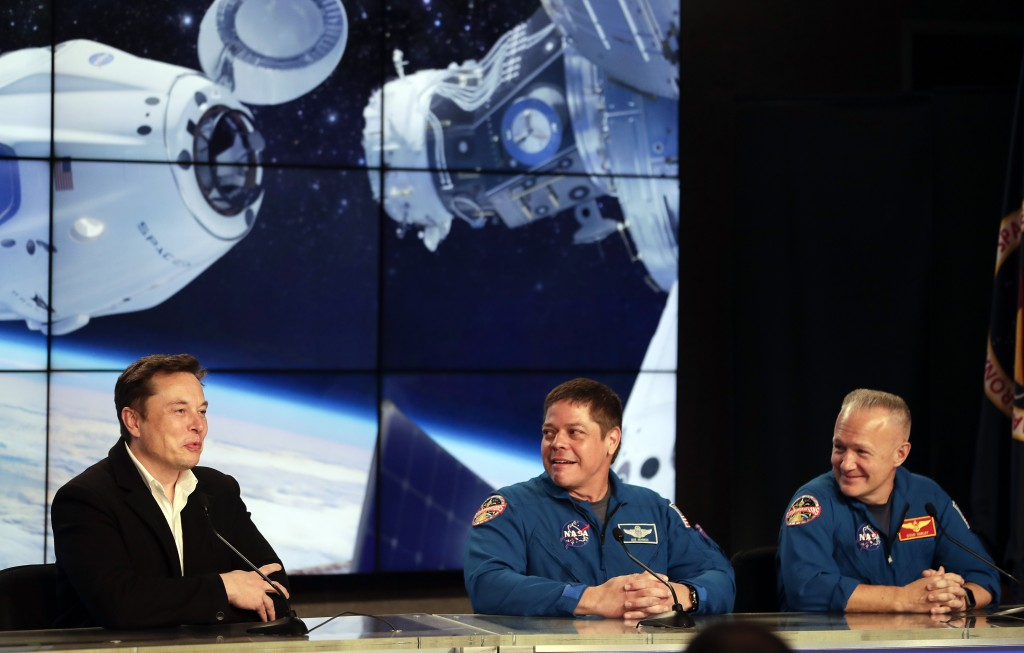 FILE - In this Saturday, March 2, 2019 file photo, Elon Musk, left, CEO of SpaceX, speaks accompanied by NASA astronauts Bob Behnken, center, and Doug...