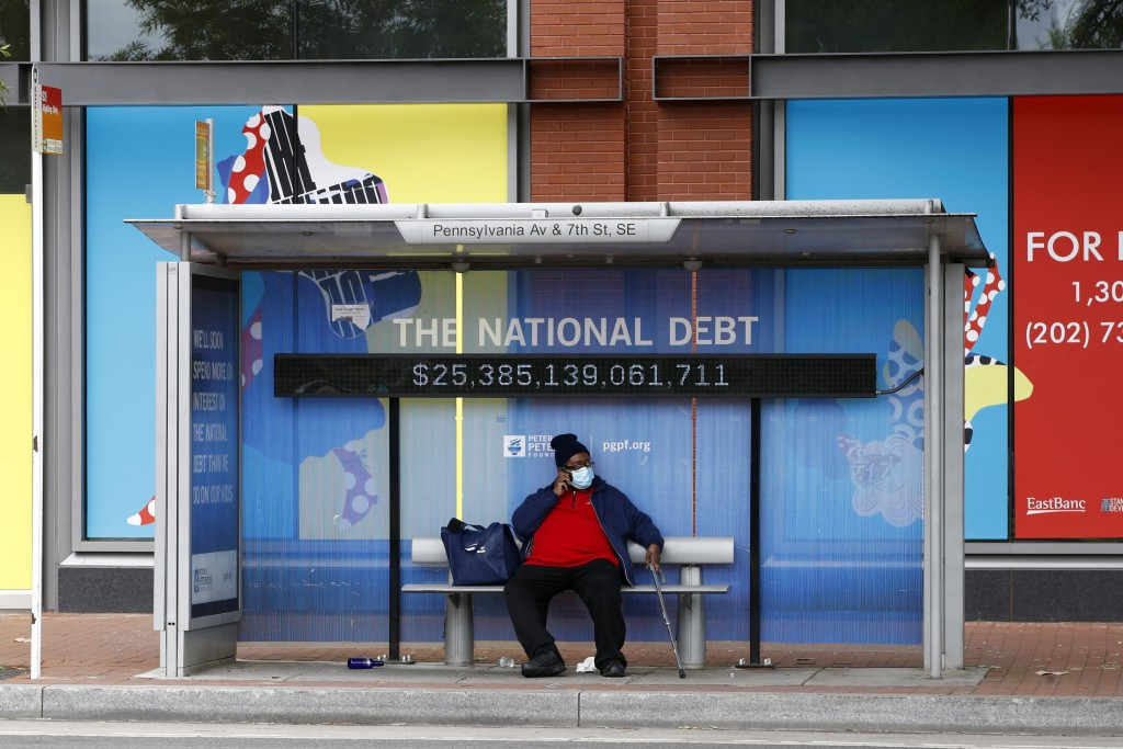 A man sits at a bus stop while wearing a face mask Thursday, May 21, 2020, in Washington. The District of Columbia is under a stay-home order for all ...