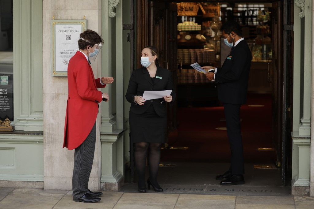 A doorman wearing a face shield and mask to protect from coronavirus is spoken to by colleagues at the main entrance of the Fortnum & Mason department...