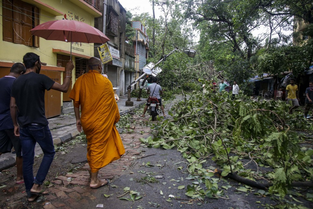 A Buddhist monk walks through a road laid with fallen trees and branches after Cyclone Amphan hit the region in Kolkata, India, Thursday, May 21, 2020...