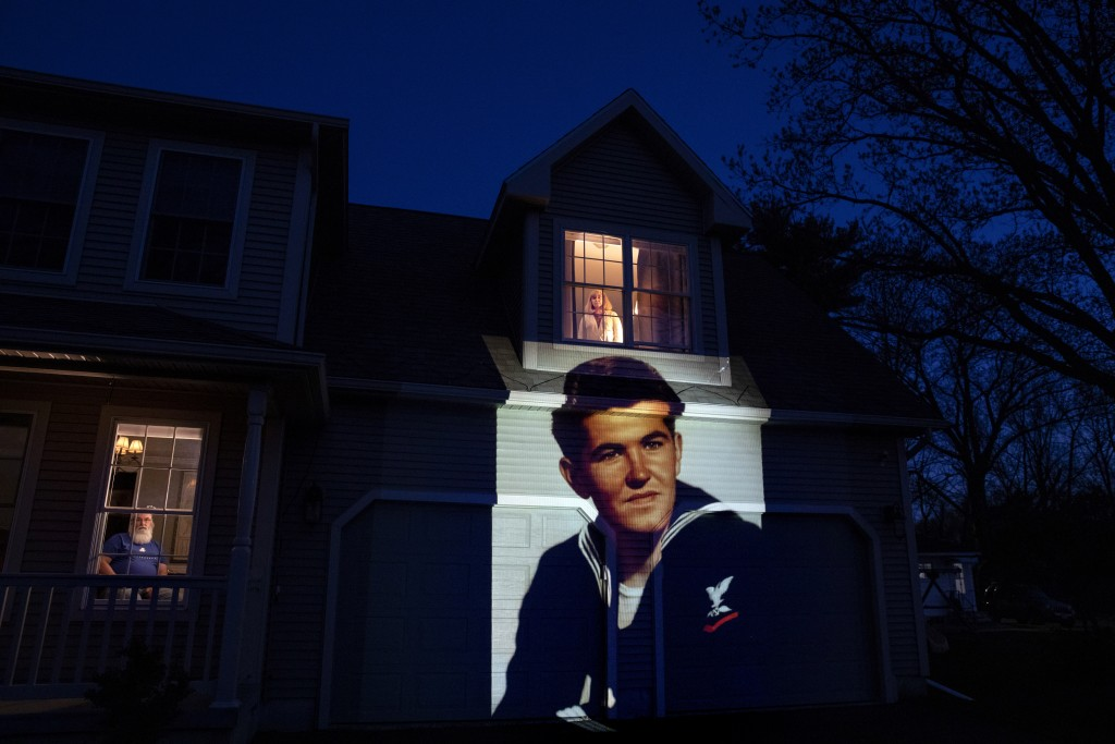 An image of veteran Stephen Kulig is projected onto the home of his daughter, Elizabeth DeForest, as she looks out the window of a spare bedroom as he...