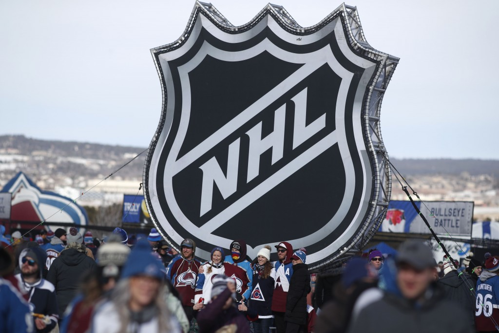 FILE - In this Saturday, Feb. 15, 2020, file photo, fans pose below the NHL league logo at a display outside Falcon Stadium before an NHL Stadium Seri...