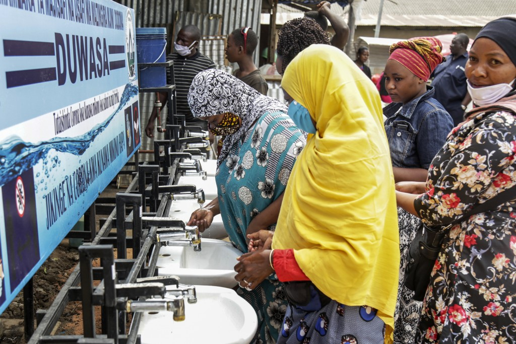 In this photo taken Monday, May 18, 2020, people use a hand-washing station installed for members of the public entering a market in Dodoma, Tanzania....