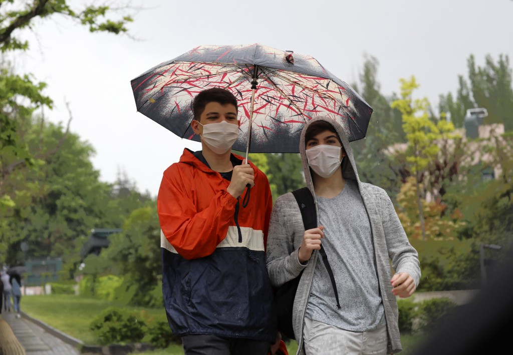 People wearing face masks for protection against the new coronavirus, walk in rain just hours before a four-day new curfew declared by the government ...
