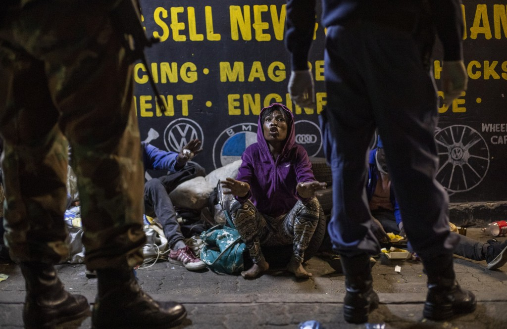 A homeless woman talks to South African Defense Forces and police officers as they patrol the street in Johannesburg, South Africa, May 1, 2020, as th...