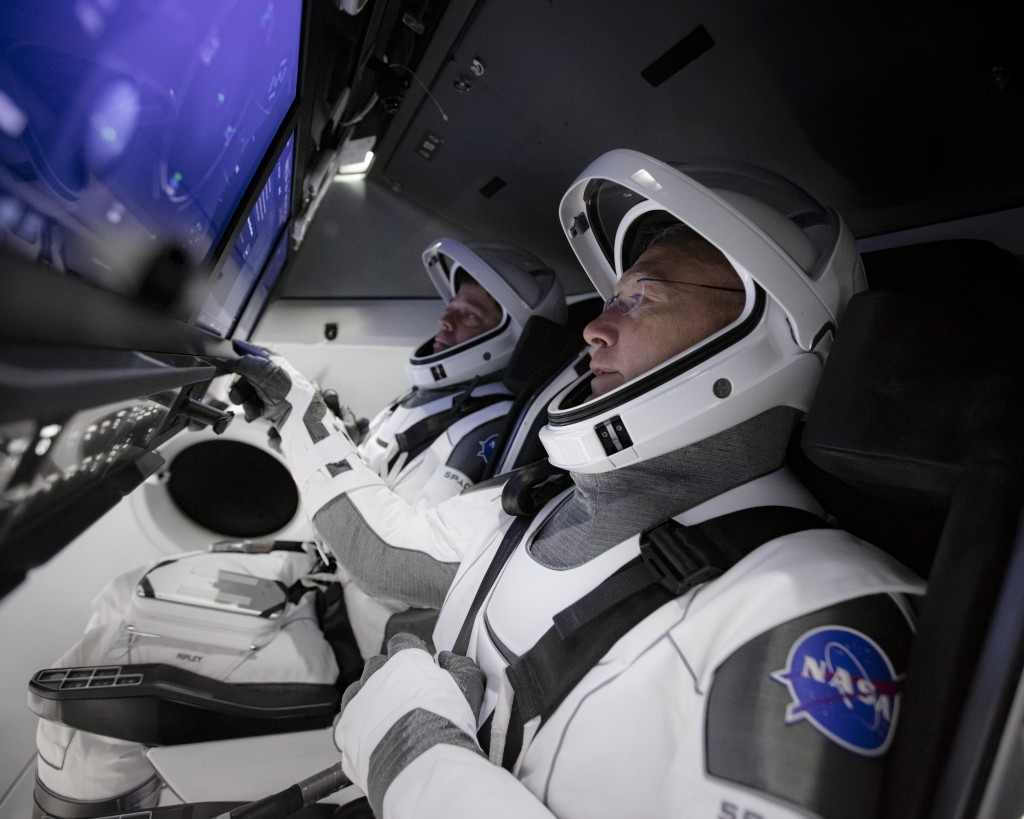 In this Thursday, March 19, 2020 photo made available by SpaceX, astronauts Doug Hurley, foreground, and Bob Behnken work in SpaceX's flight simulator...
