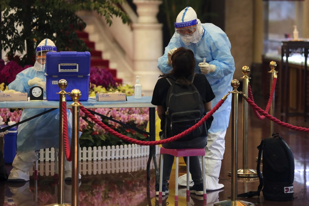 A medical worker takes a swab from a foreign reporter who was selected to cover the opening ceremony of the Chinese People's Political Consultative Co...