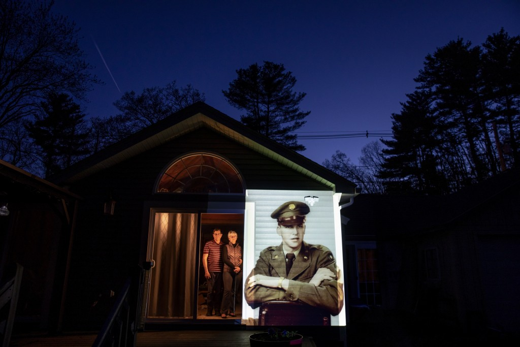 An image of veteran Roy Benson is projected onto the home of his daughter, Robin Benson Wilson, left, as she looks out a doorway with her husband, Don...