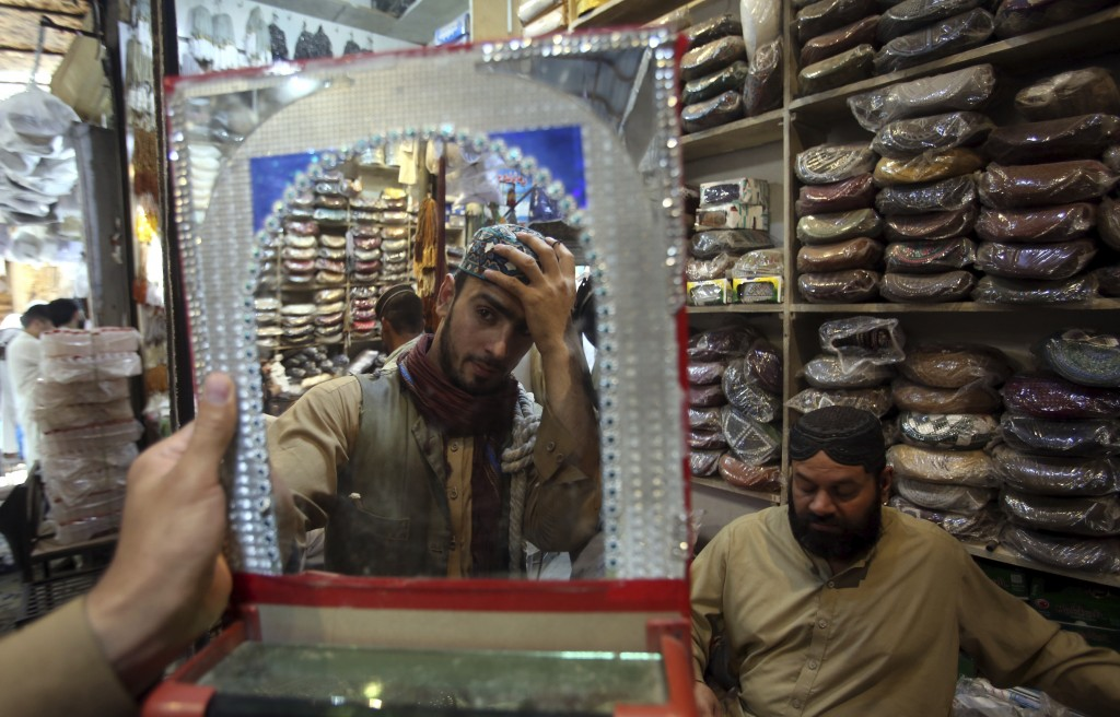 A customer tries a traditional cap for the upcoming Eid al-Fitr holiday that marks the end of the Muslim holy fasting month of Ramadan after the gover...