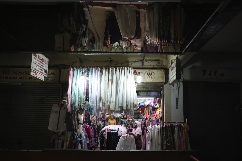Cloth venders prepare to open their shops amid fears of the new coronavirus outbreak at a market in Jakarta, Indonesia Friday, May 22, 2020. (AP Photo...