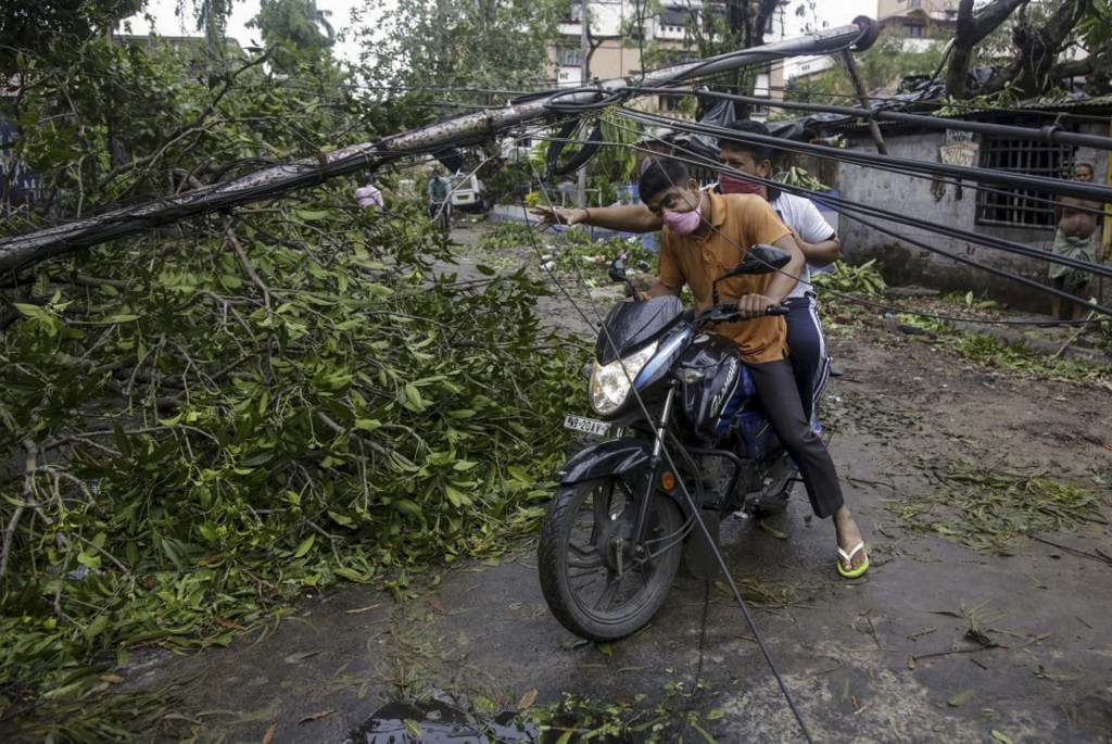 Motorists make their way through damaged cables and a tree branch fallen in the middle of a road after Cyclone Amphan hit the region in Kolkata, India...