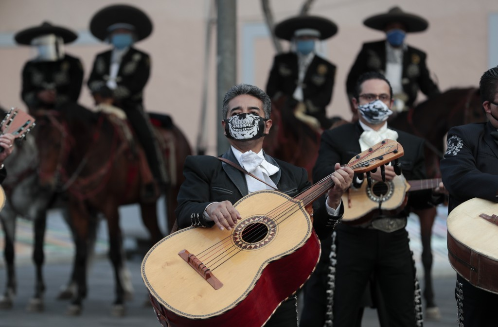 Mariachi musicians wear masks amid the new coronavirus pandemic as they play a serenade at Garibaldi square, now empty of visitors, in Mexico City, Th...