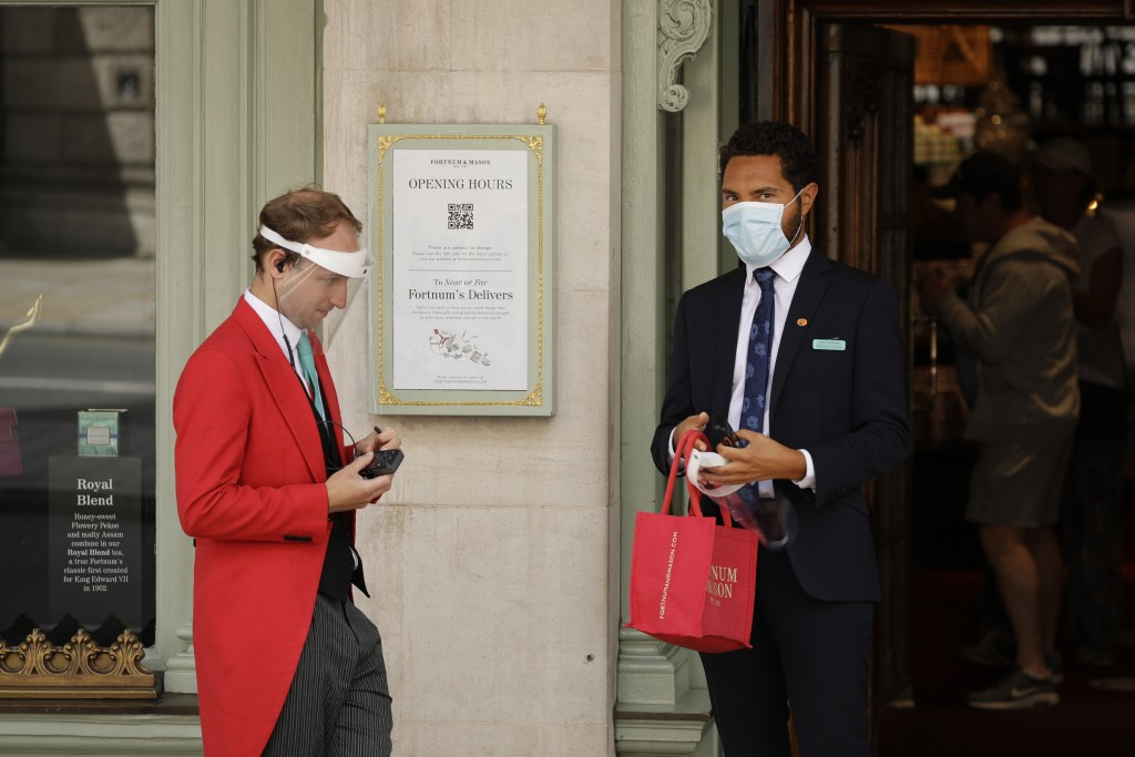 A doorman wearing a face shield to protect from coronavirus stands with a colleague at the main entrance of the Fortnum & Mason department store in th...