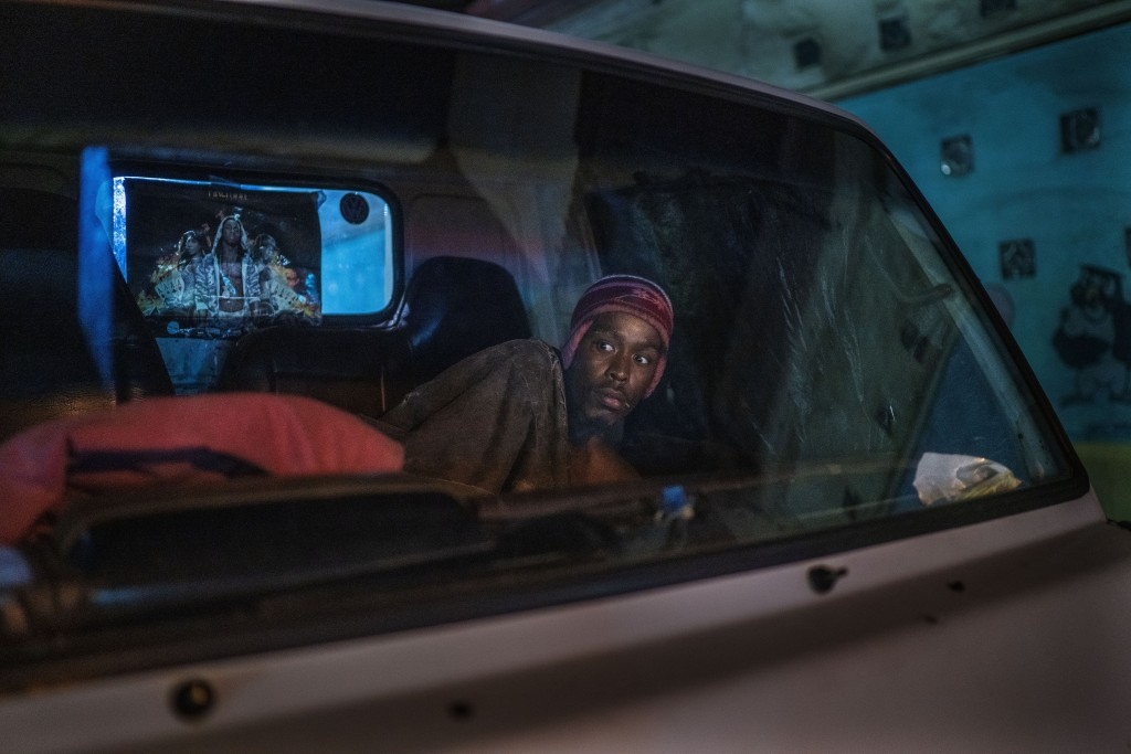 A man living in his car reacts to police and army patrolling downtown Johannesburg, South Africa, March 27, 2020. Police and army started patrolling m...
