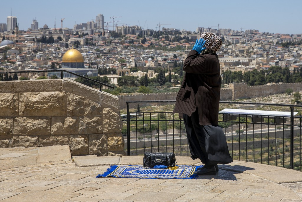 FILE - In this May 1, 2020, file photo, a Muslim woman wears gloves prays in east Jerusalem's Mount of Olives, overlooking the Dome of the Rock and al...