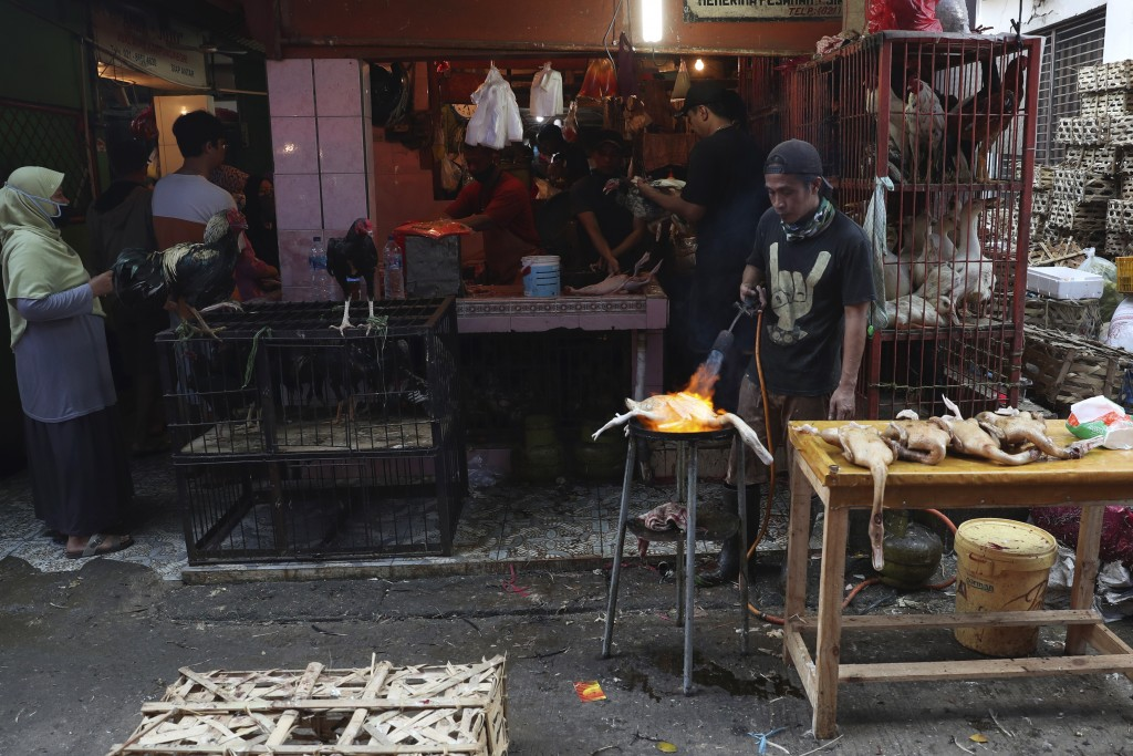 A chicken vendor burns ducks for costumer in preparation of the upcoming Eid al-Fitr holiday that marks the end of the holy fasting month of Ramadan a...