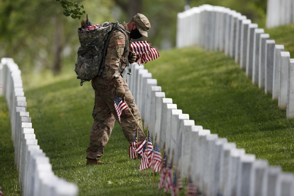 """A member of the 3rd U.S. Infantry Regiment also known as The Old Guard, wears a face mask as he places flags in front of each headstone for """"Flags-In""""..."""