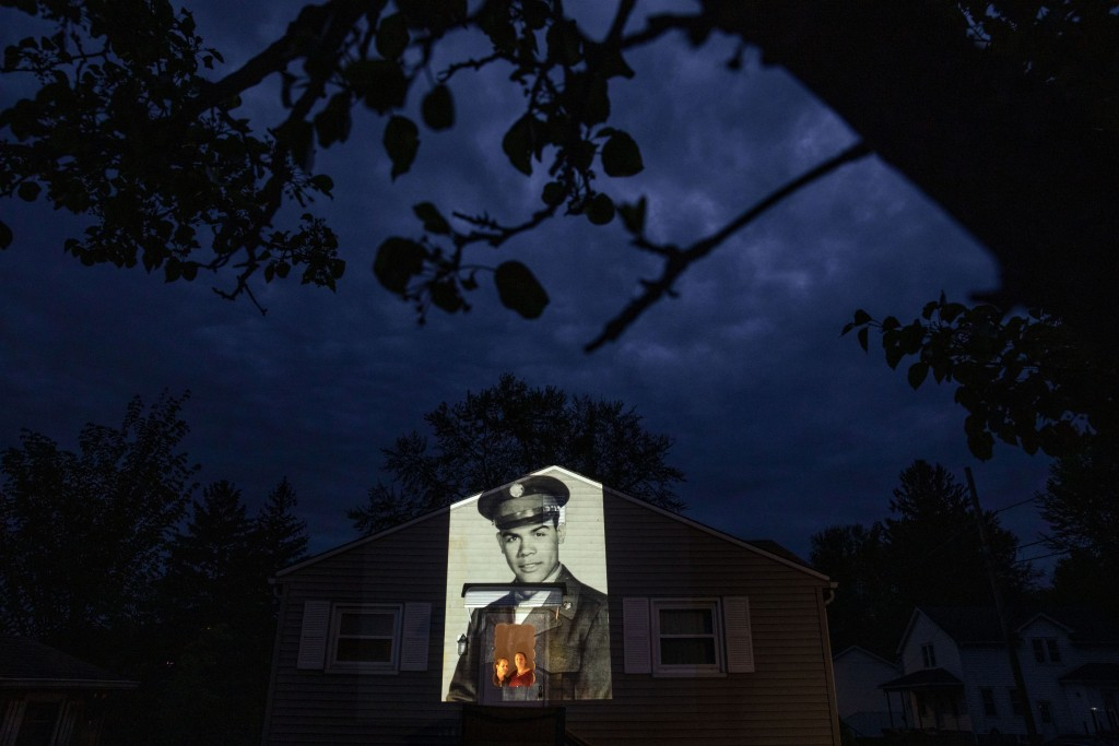 An image of veteran Samuel Melendez is projected onto the home of his nieces, Janet Ramirez, right, and Mary Perez, as they look out a doorway in Chic...